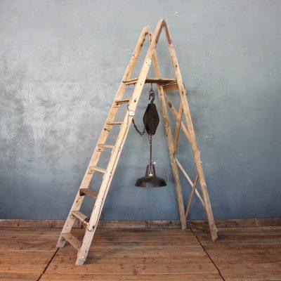 Lampada realizzata con una scala in legno di abete e lampada industriale nera in metallo